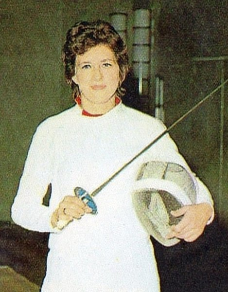 An old photo of Ujlaky-Rejto Ildiko holding a fencing foil and a helmet. She is in a white fencing jumpsuit.
