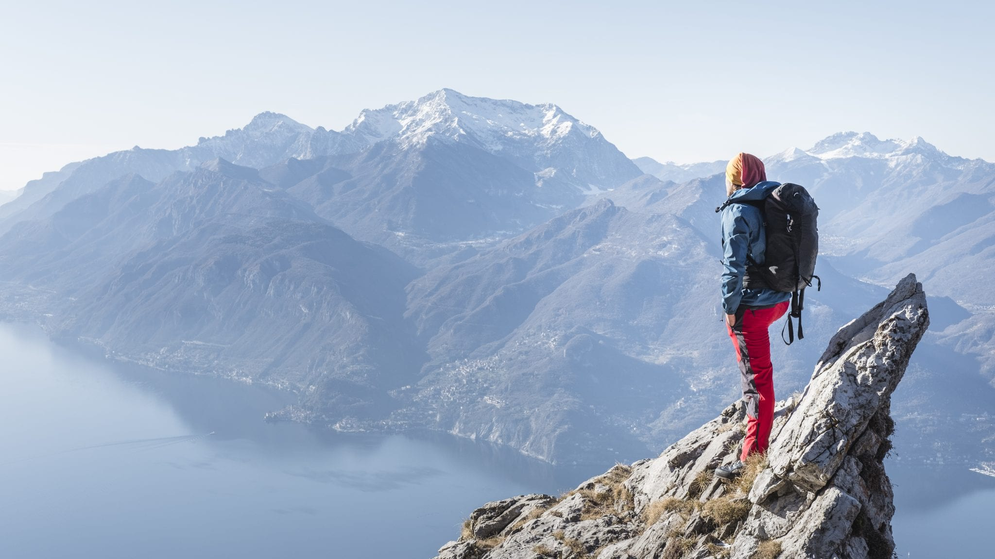 Heidi Zimmer standing at the top of a tall mountain looking out over an expanse of sea and rocky mountains.